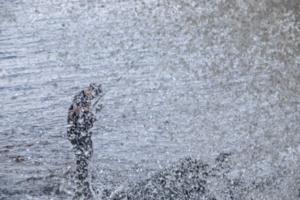 рыбак в брызгах падающей воды
